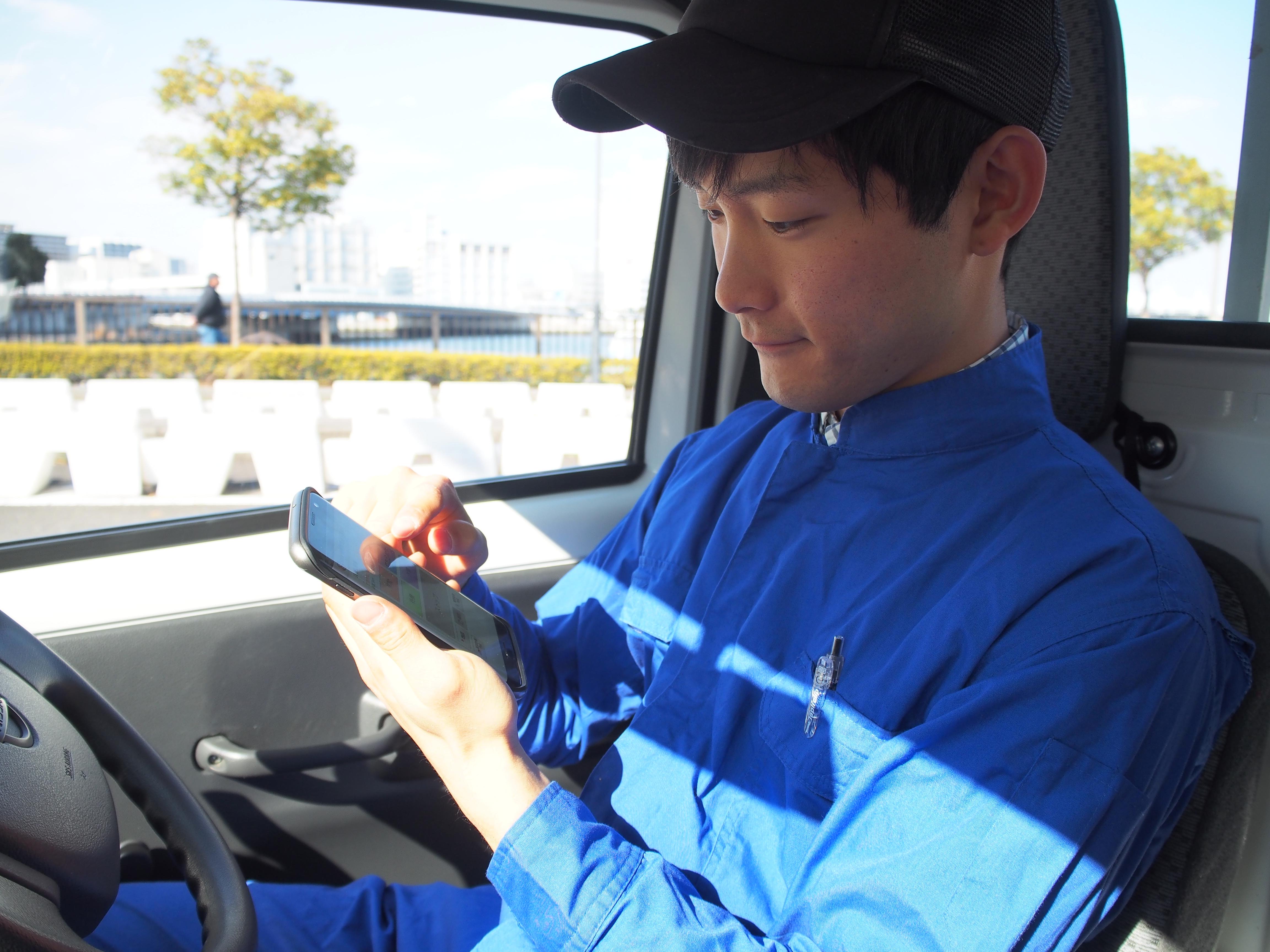 スマートフォンを操作するドライバー